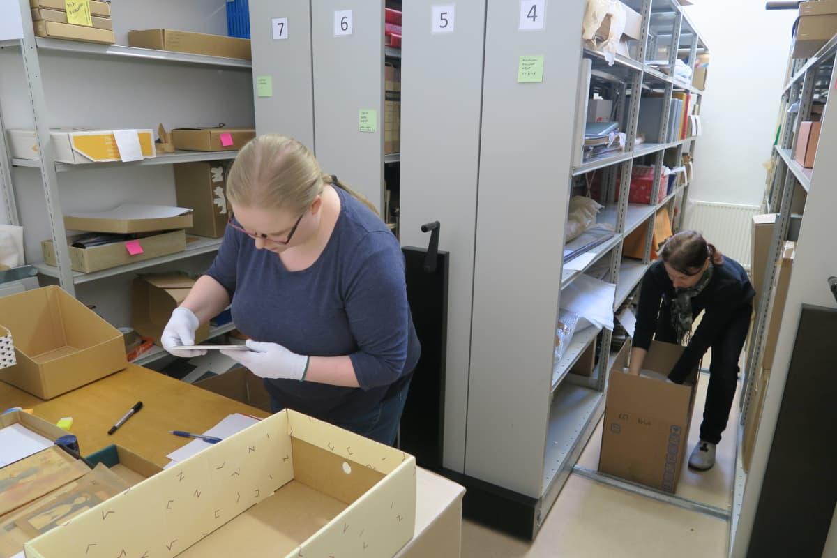 Opasvalvoja Ami Kallo ja amanuenssi Heidi Pelkonen pakkaavat arkistokokoelmia.