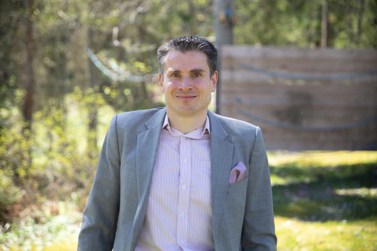 Nordean pääanalyytikko Jan von Gerich seisoo ulkona puvun paidan kaulus rennosti auki ja katsoo kameraan.