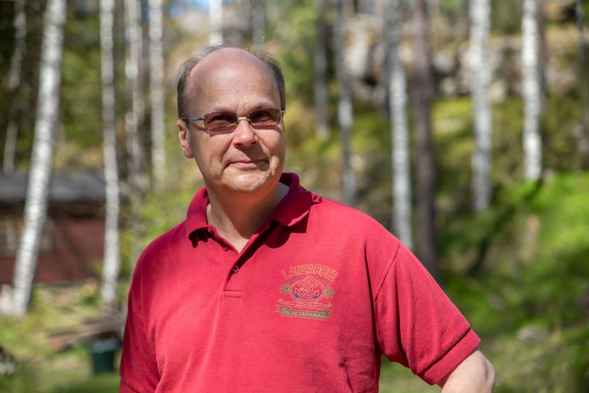 Ekonomisti Roger Wessman seisoo ulkosalla tummat lasit silmillään yllään lyhythihainen punainen pikeepaita.