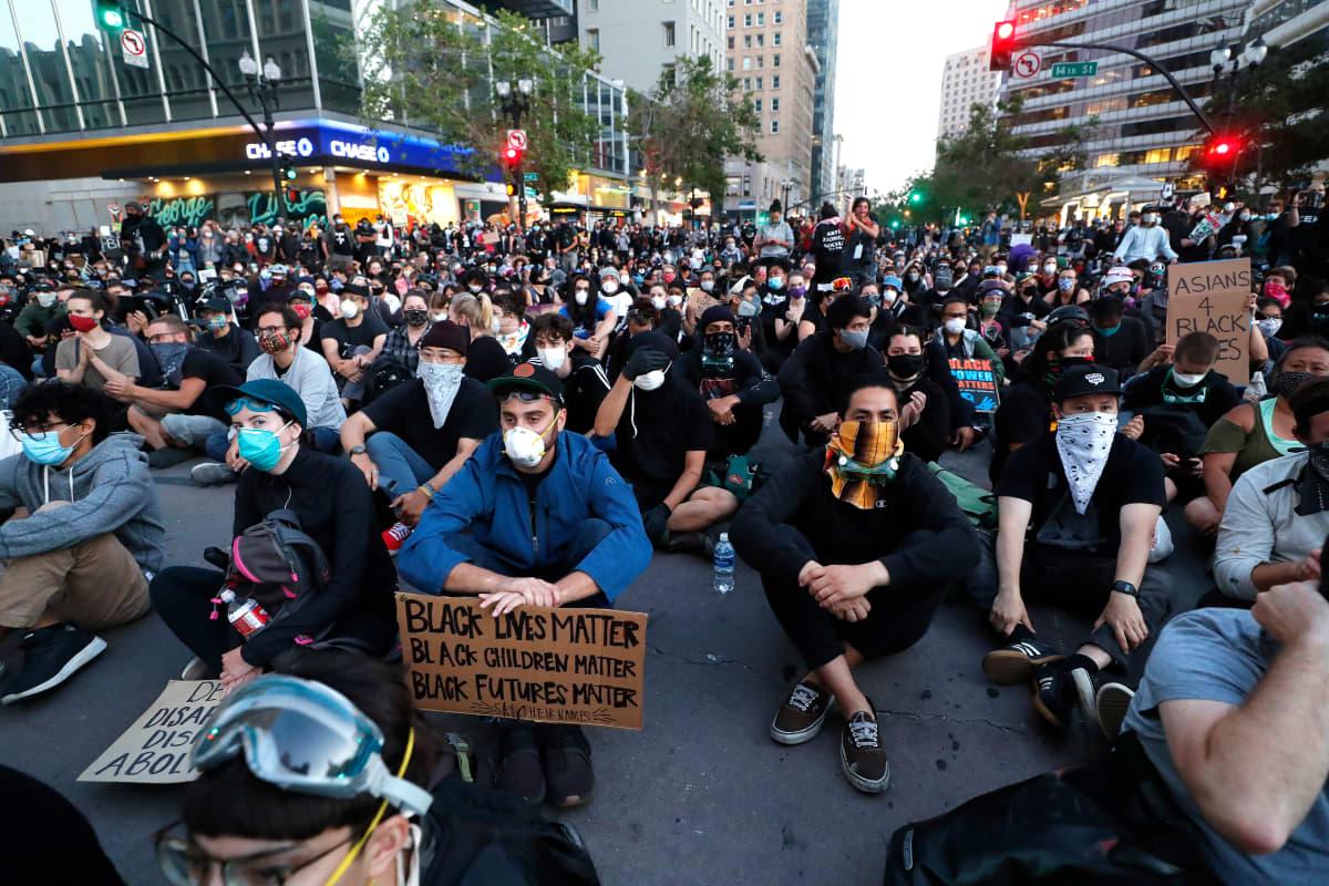 Mielenosoittajat istuvat kadulla