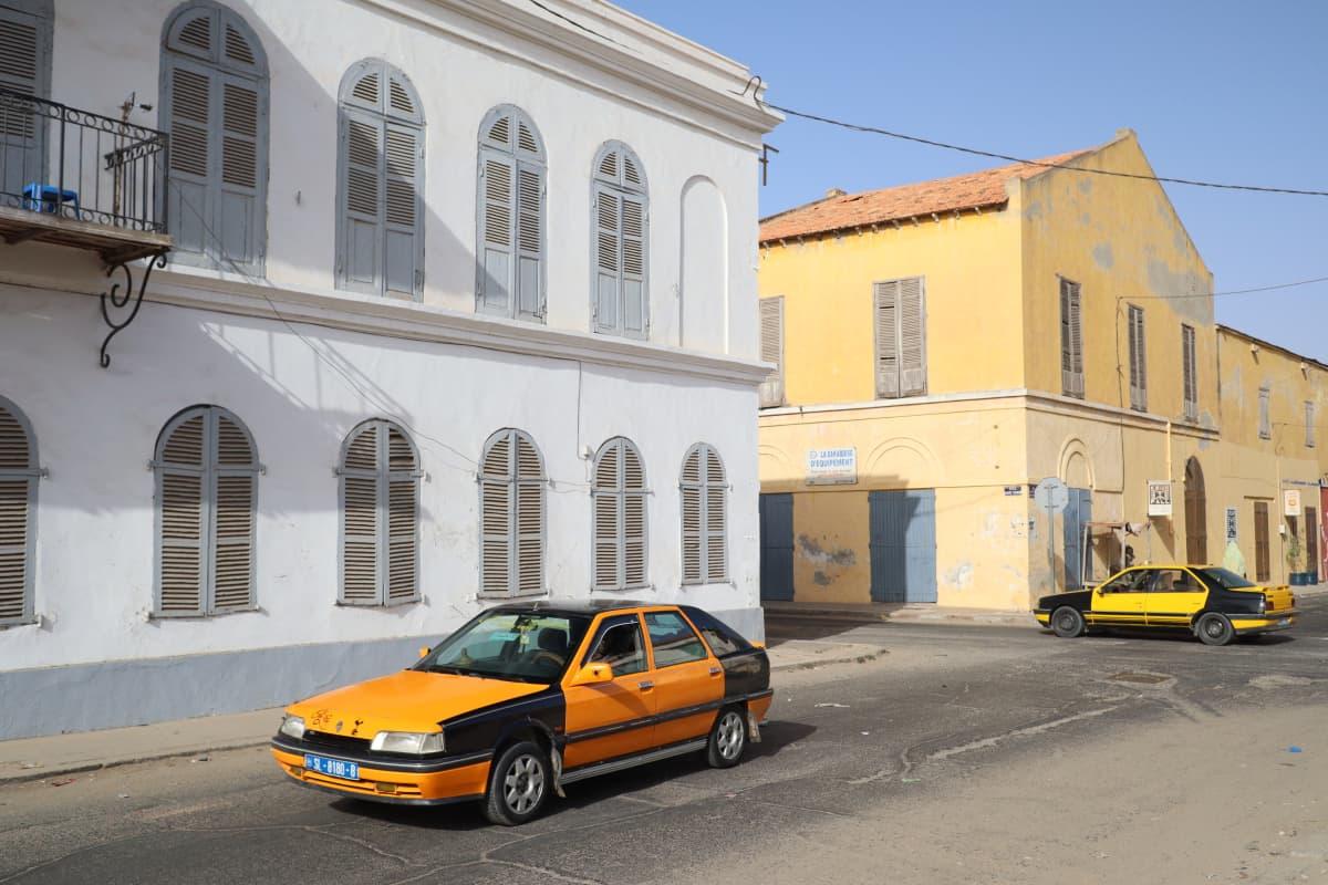 Kaksi siirtomaatyylistä rakennusta ja kaksi keltamustaa autoa Saint-Louis'n vanhankaupungin kaduilla.