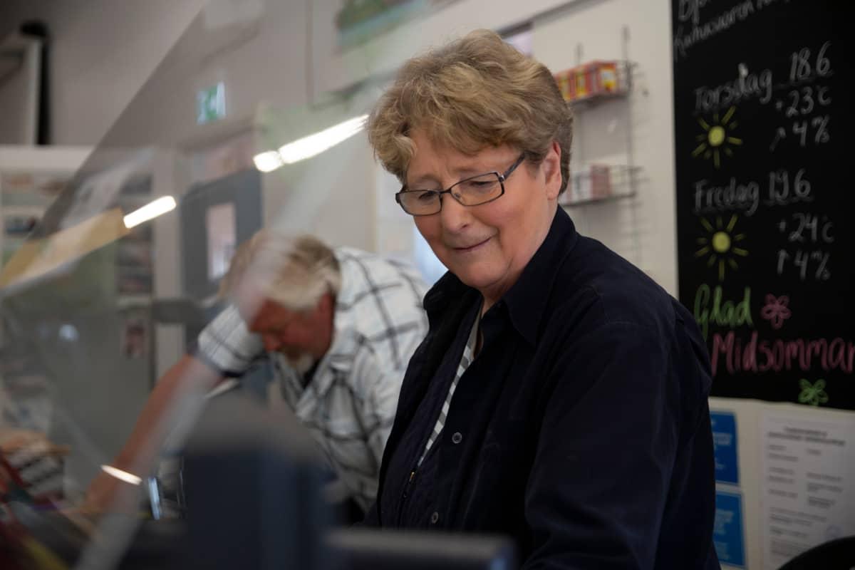 Kauppalaiva Christinan yksi omistajista on Siv Ahonen naputtelee tuotteiden hintoja kassakoneeseen. Taustalla on kippari Enska Myllylä.