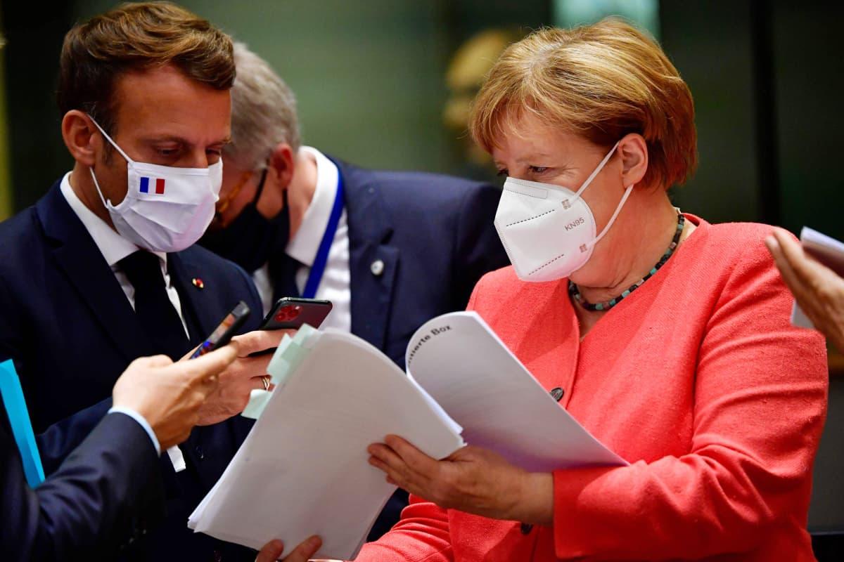 Ranskan presidentti Emmanuel Macron ottaa puhelimellaan kuvaa dokumentista, jota Saksan liittokansleri pitää käsissään EU:n huippukokouksessa. Kummallakin on kasvomaski.