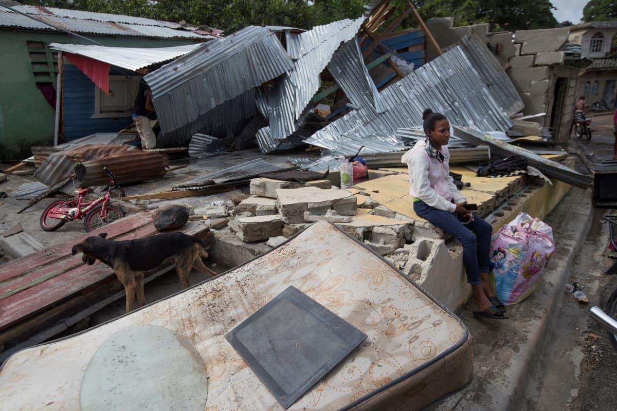 Nainen istuu tuhoutuneen rakennuksen raunioiden keskellä