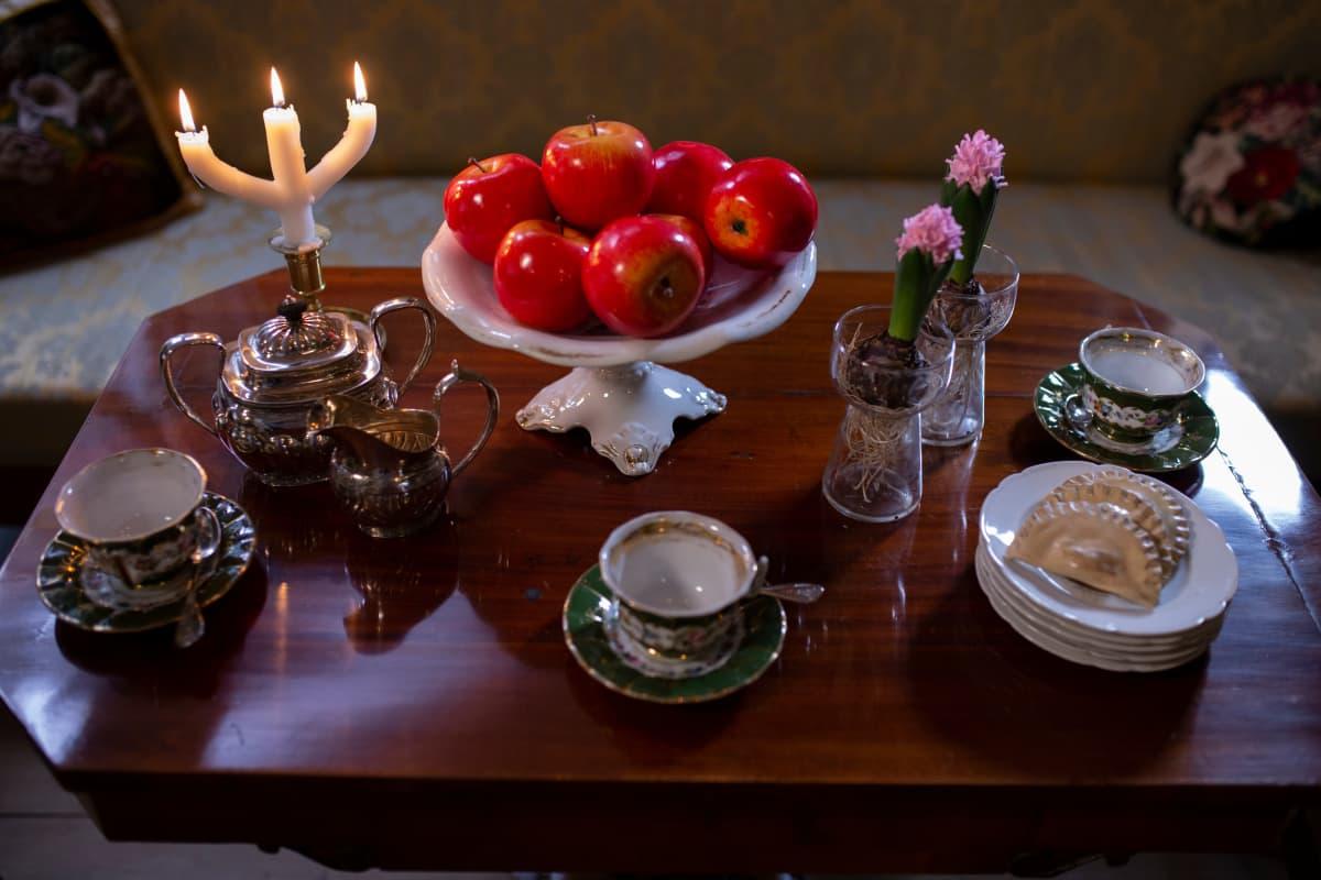 Vanhanaikainen kahvipöytä, jolla hyasintteja hyasinttilaseissa.