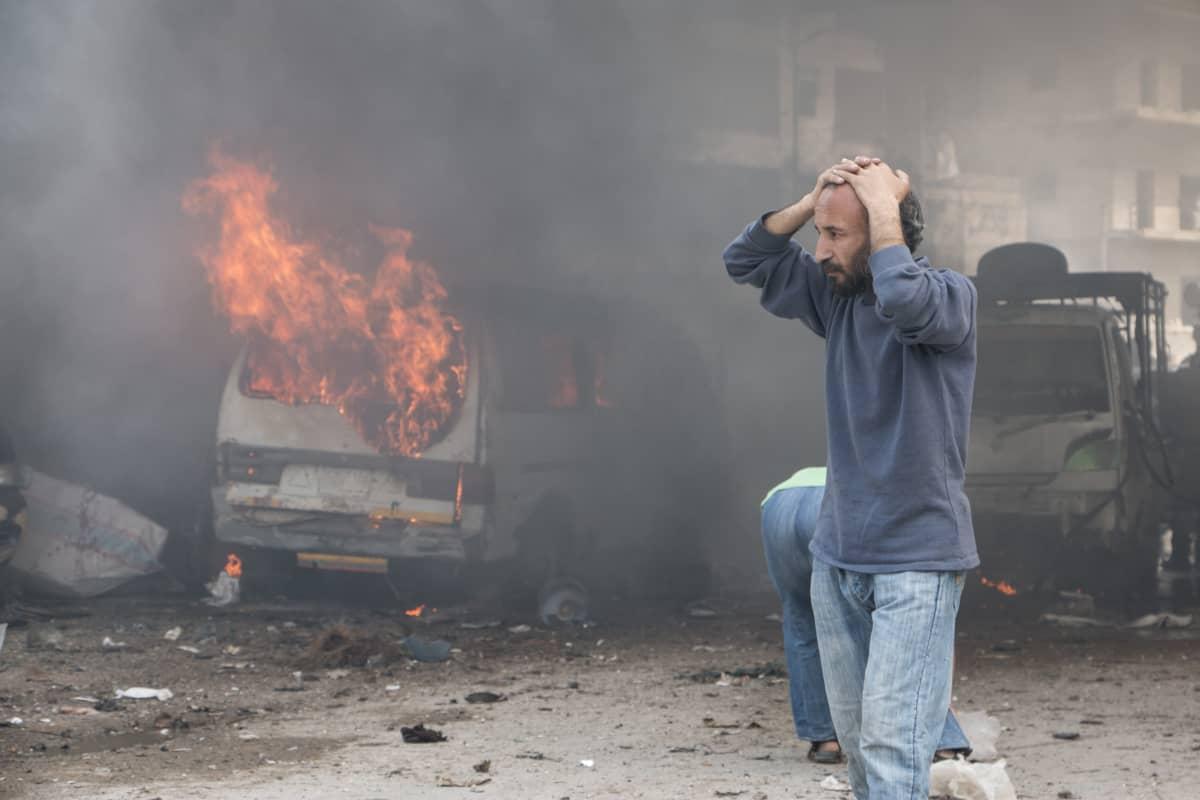 Mies seuraa järkyttyneenä kun talo palaa Aleppossa.