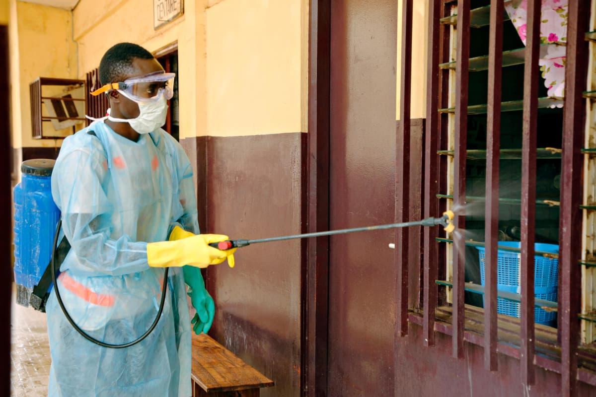 Guinean Punaisen Ristin vapaaehtoiset desinfioivat sairaalaa Guinean pääkaupungissa Conakryssa huhtikuussa 2014.