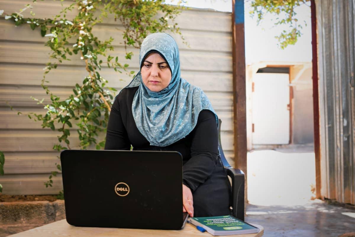Rana Ibrahim Alsees käyttää kannettavaa tietokonetta Zaatarin pakolaisleirillä Jordaniassa.