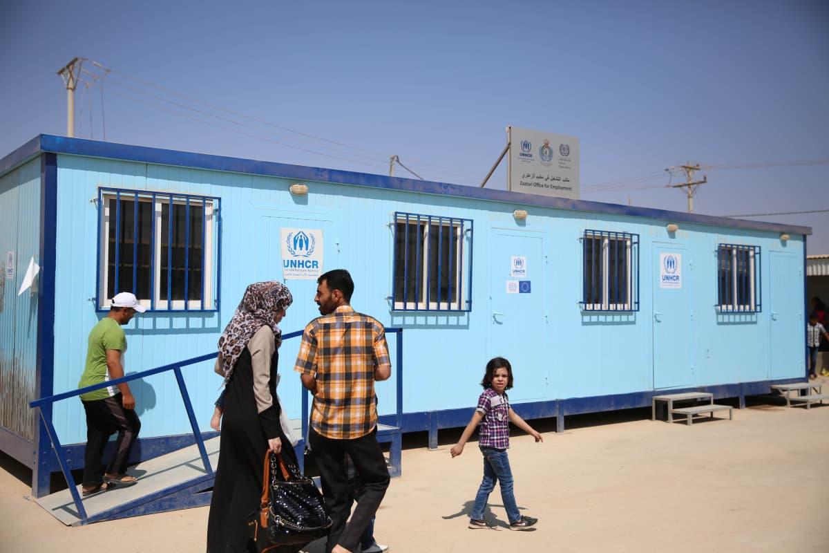 Ihmisiä YK:n pakolaisjärjestö UNHCR:n toimipisteen edessä Zaatarin pakolaisleirillä.
