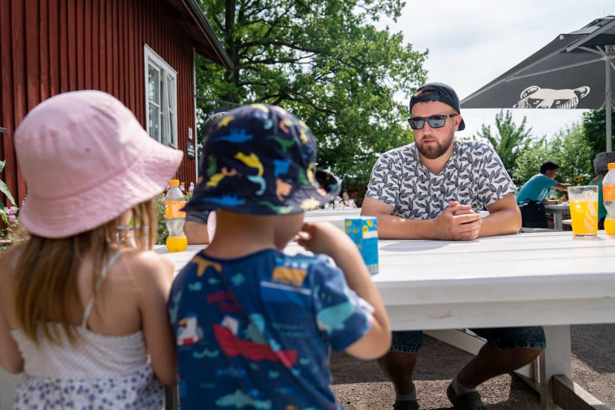 Isä Jesse Vänskä lastensa kanssa juomassa mehua.