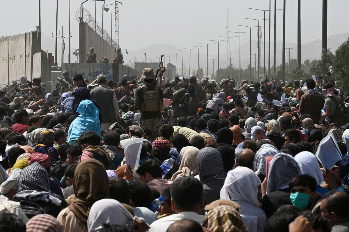 Afganistanilaiset yrittävät päästä kentälle.