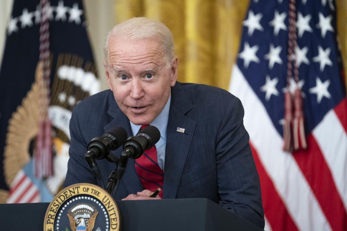Presidentti Joe Biden puhuu, pieni virne kasvoilla.