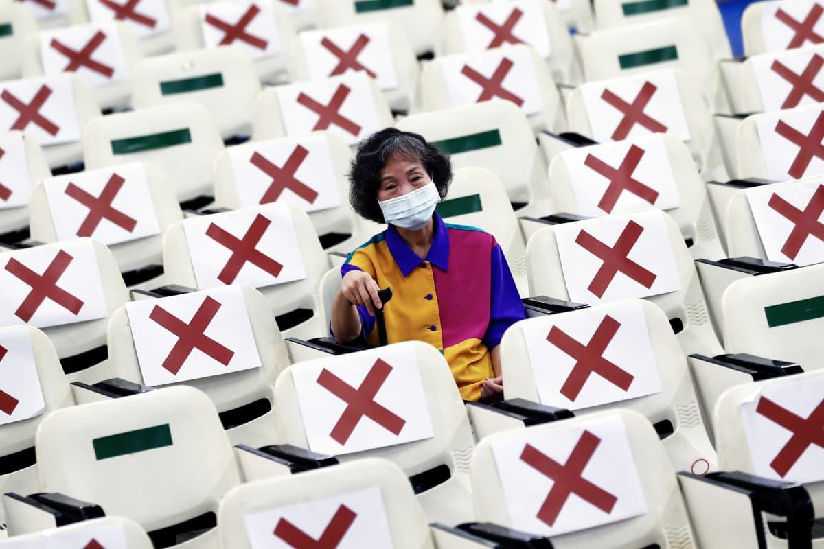 Juuri rokotuksen saanut kasvomaskiin pukeutunut henkilö istuu odottamassa mahdollisia sivuvaikutuksia rokotuskeskuksessa Taiwanissa.