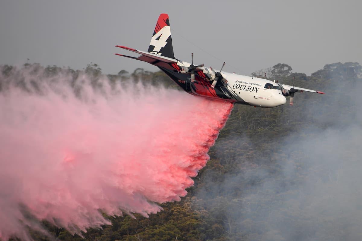 Lentokone levittää vaaleanpunaista sammutusainetta.