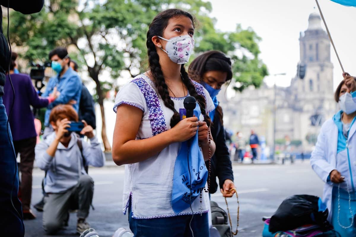 Meksikolainen nuori nainen rukoilee kadulla mielenosoituksessa, kädessään huivi, rukousnauha ja mikrofoni.