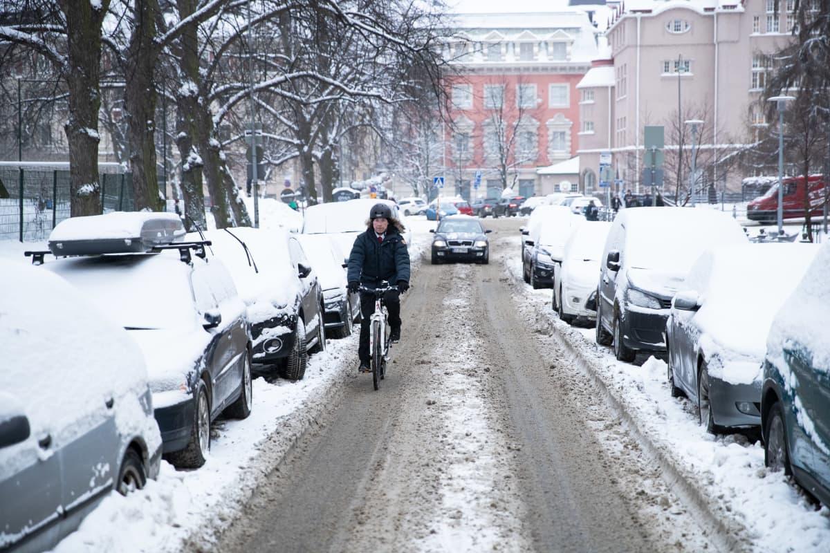 Jussi Halla-aho pyöräilee lumisella kadulla