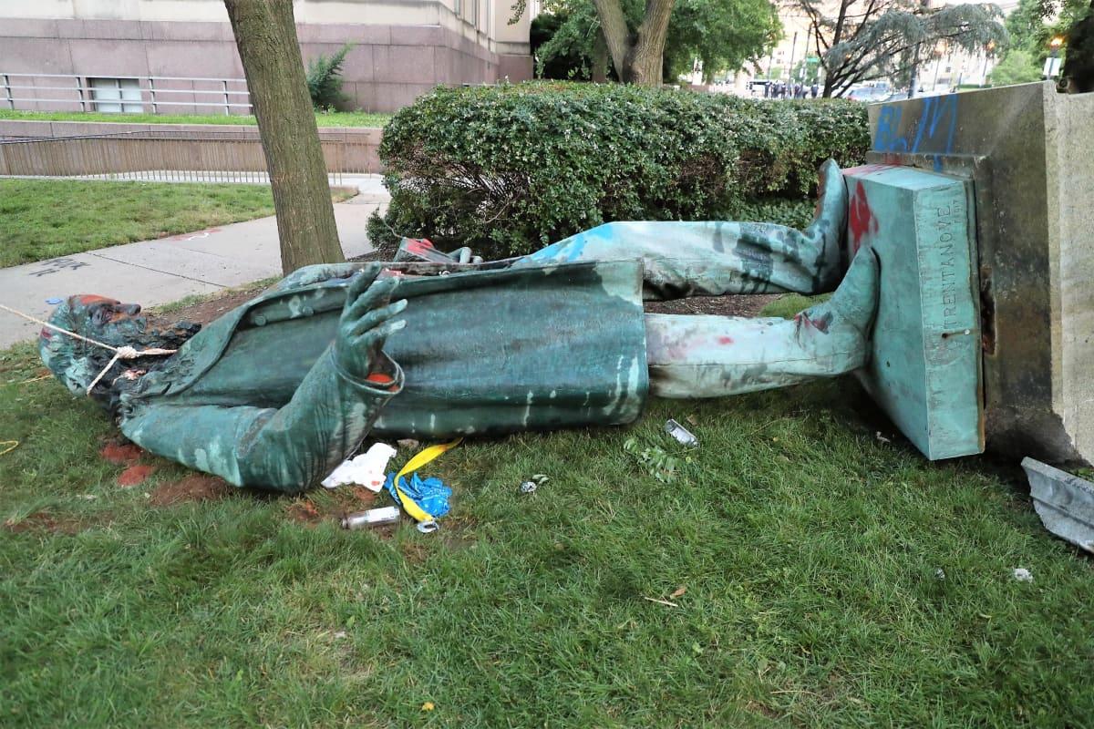 Albert Piken kaadettu patsas makaa maassa nurmikolla, patsaan kaulassa on köysi. Patsasta on töhritty punavärillä.