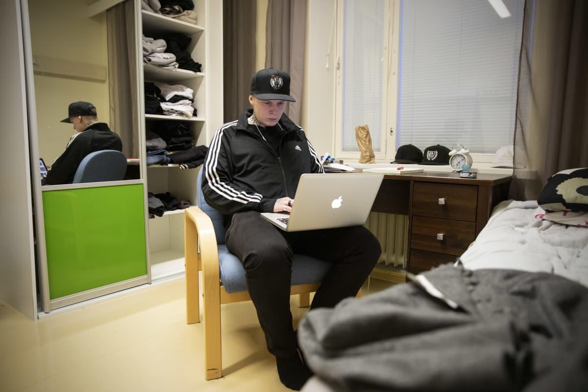 Patrik Lindblom istuu tuolilla ja käyttää läppäriä.