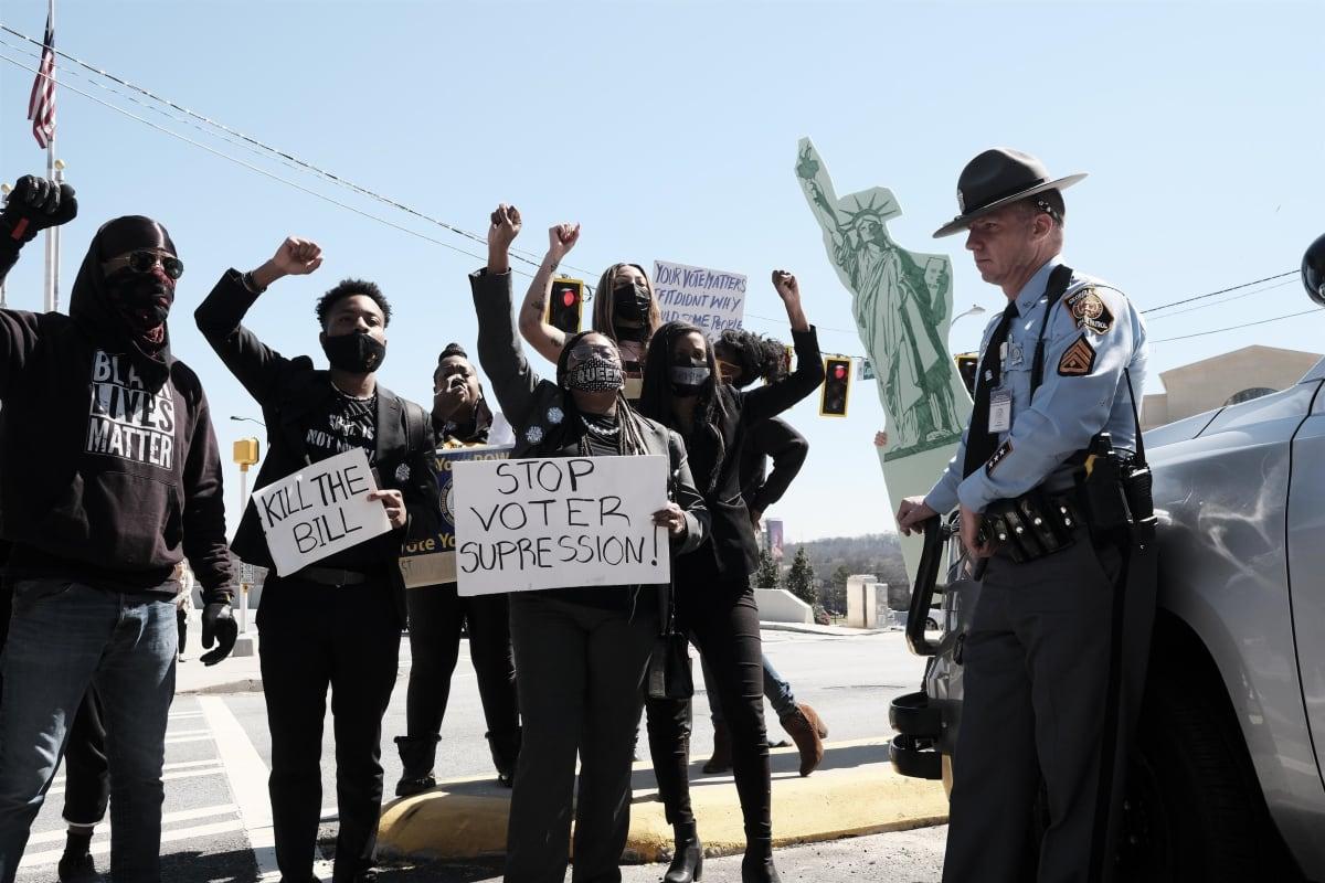 Joukko mustia mielenosoittajia käsi pystyssä kylttien kanssa. Oikealla kuvassa lierihattuinen poliisi valvoo.