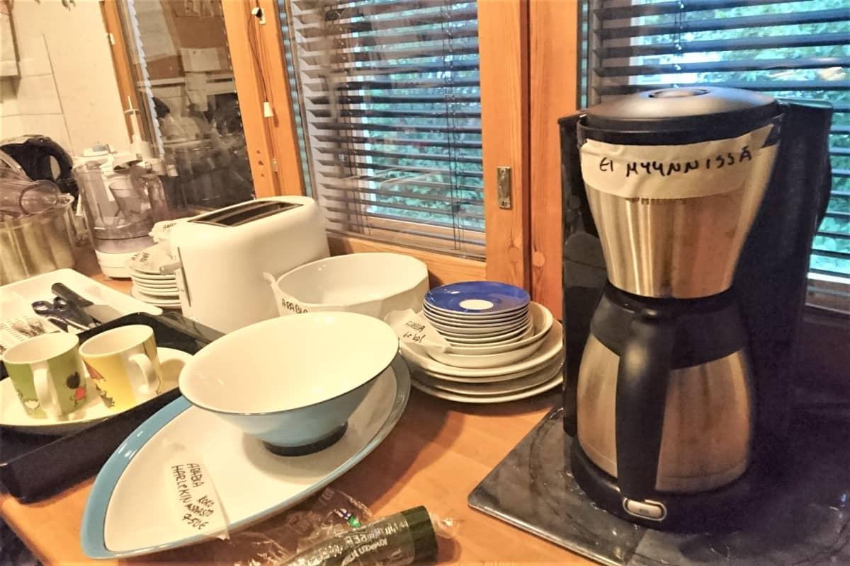"""Astioita ja kahvinkeitin pöydällä. kahvinkeittimessa lappu """"Ei myynnissä""""."""