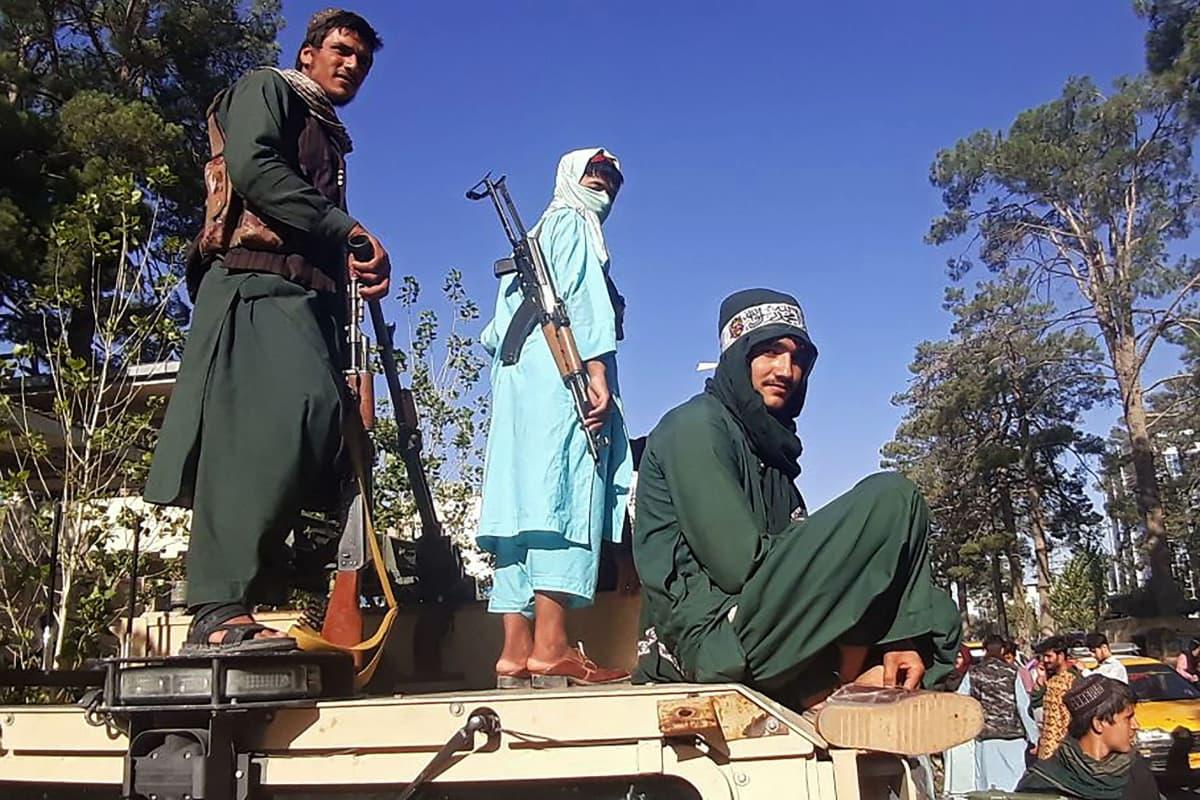 Taliban-taistelijat seisovat ajoneuvon päällä.