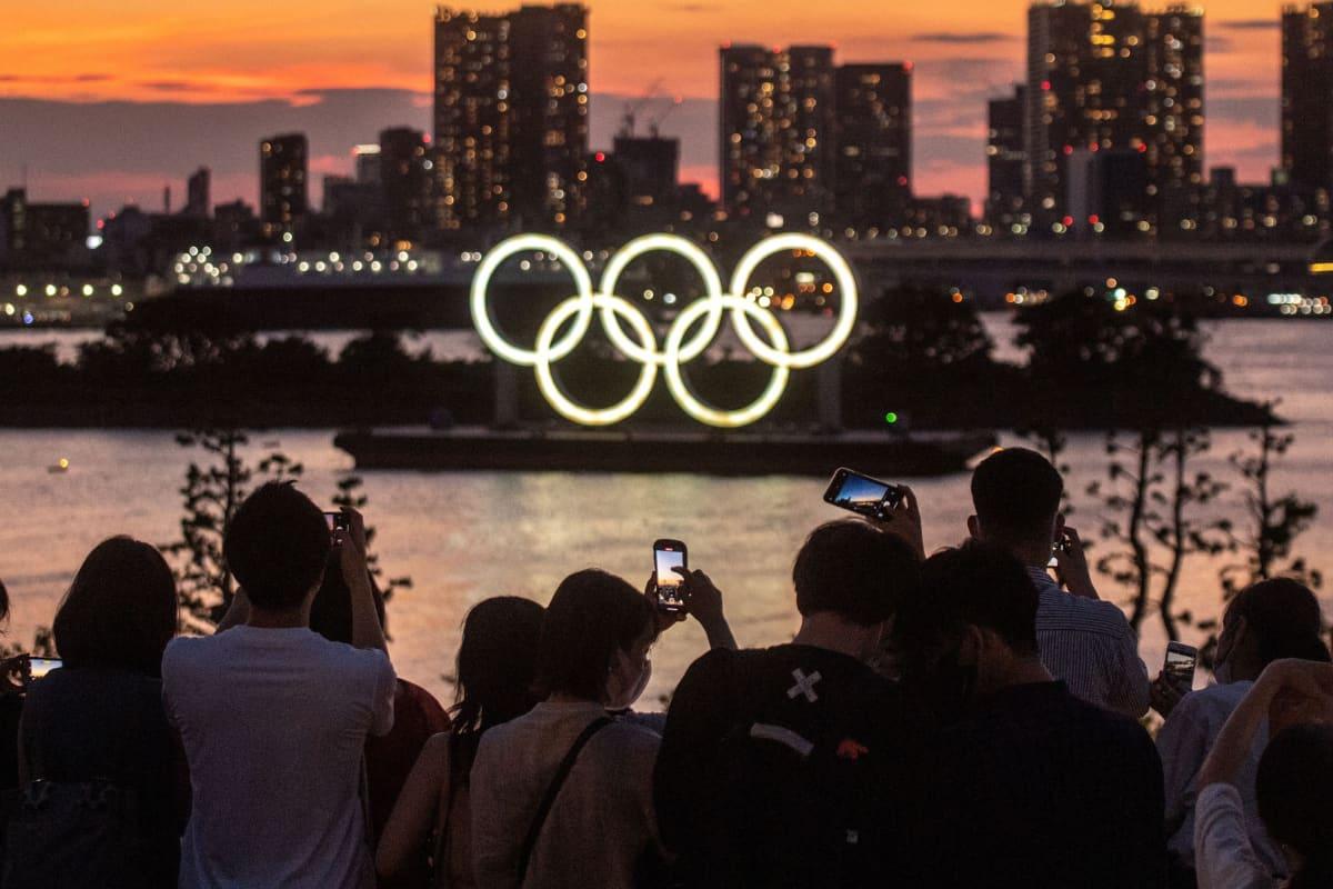 Ihmiset kuvaavat valaistuja olympiarenkaita auringon laskiessa Tokiossa 22. heinäkuuta.