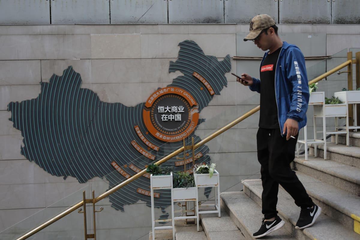 Mies kävelee puhelintaan selaillen Evergrande ostoskeskusken portailla.