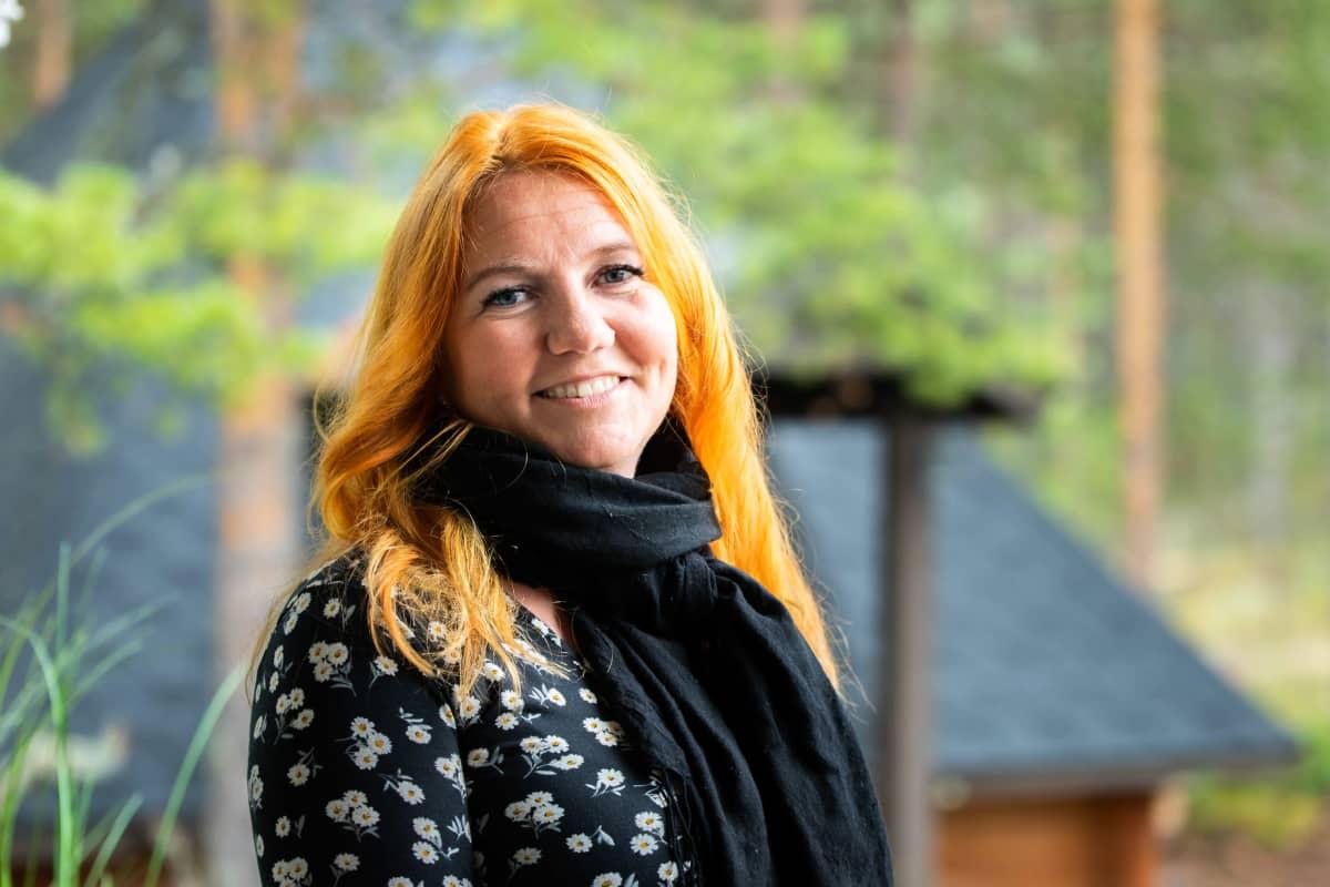 Oranssihiuksinen nainen, Mari Lappalainen, tummassa kukkapaidassa katsoo kameraan. Taustalla häämöttää kesäinen maisema.