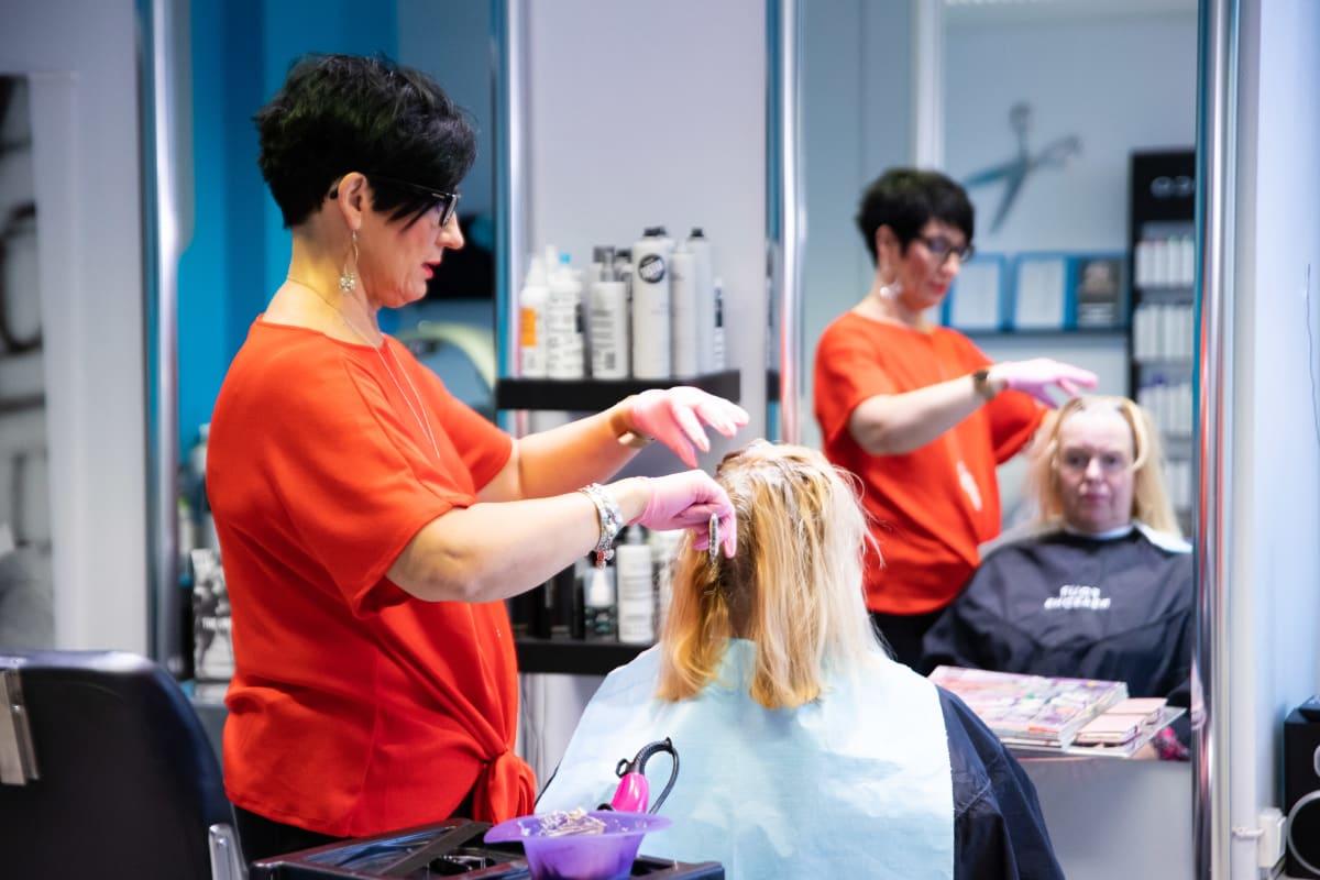 Kampaaja levittää väriä asiakkaan hiuksiin.