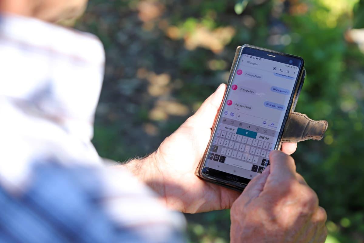 Henkilön kädessä puhelin, jonka näytöllä on tekstiviestejä.