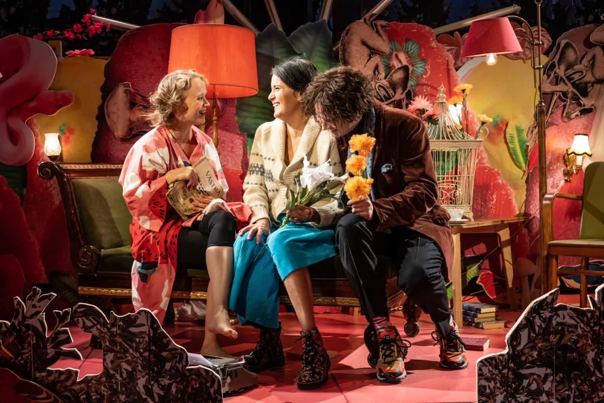 Kuvassa on kolme näyttelijää istumassa: Ella Mettänen, Vilma Melasniemi ja Miiko Toiviainen. He nauravat.