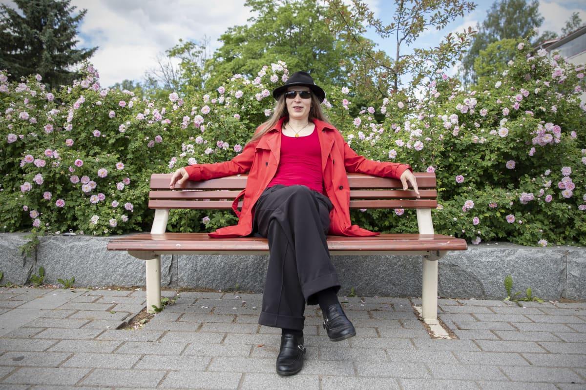 Alia Dannenberg istuu penkillä ruusupensaiden edessä.