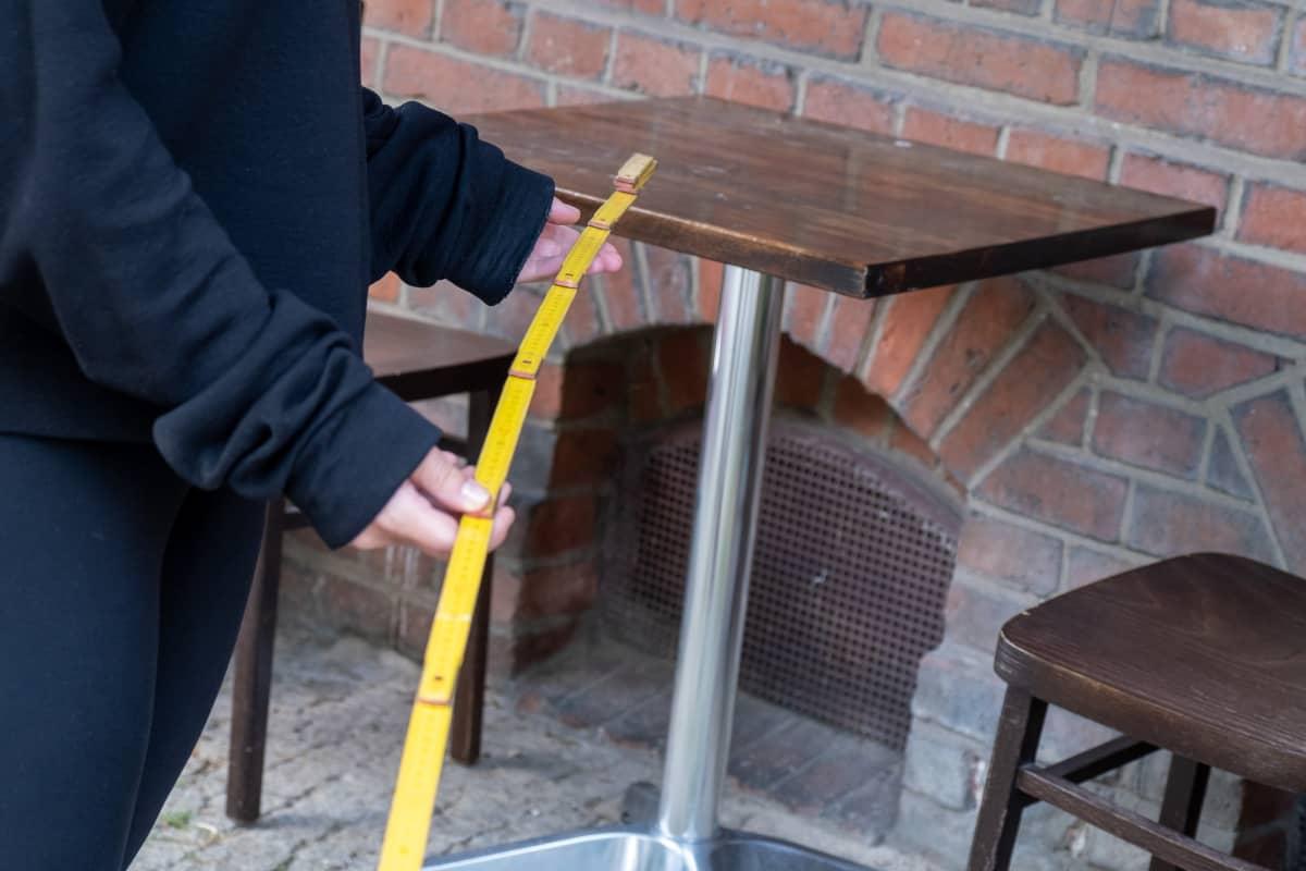 Terassilla oleva ravintolapöytä ja mittaa pitelevät kädet.
