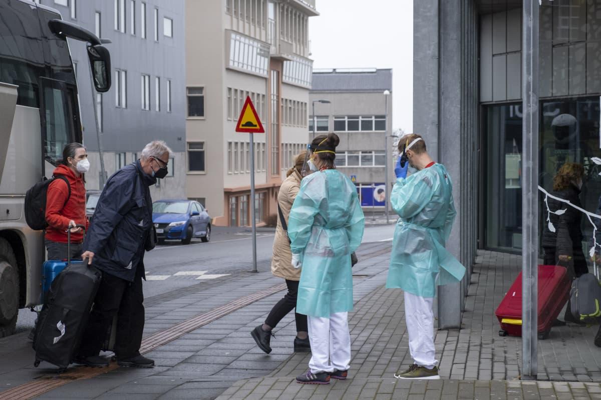 Matkailijoita ja suojavarusteissa olevia terveydenhuollon työntekijöitä.