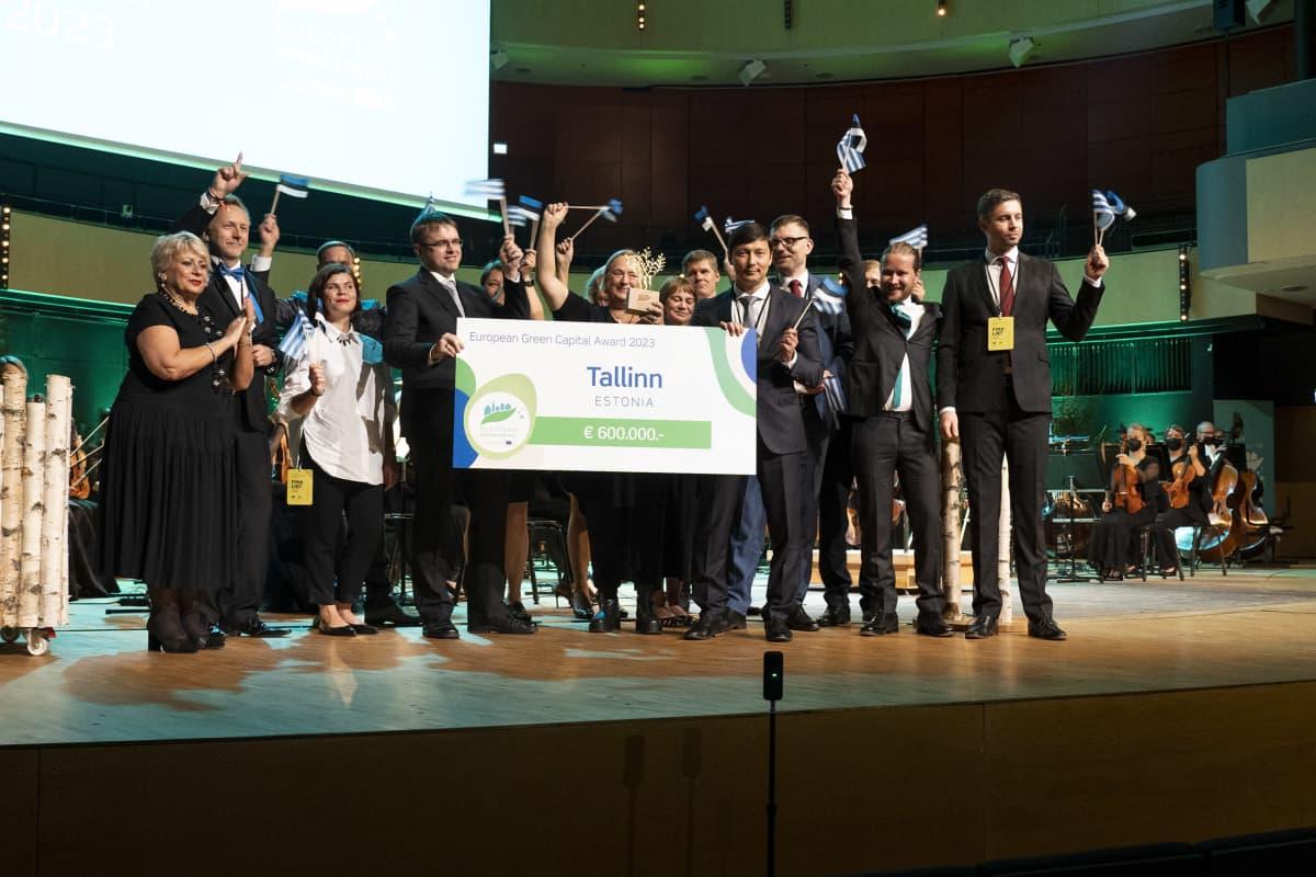Lavalla seisovia ihmisiä. Ihmiset heiluttavat käsissään pieniä viron lippuja. Keskellä olijat pitelevät suurta korttia, johon on kirjoitettu muun muassa Tallinna ja 600 000 euroa.