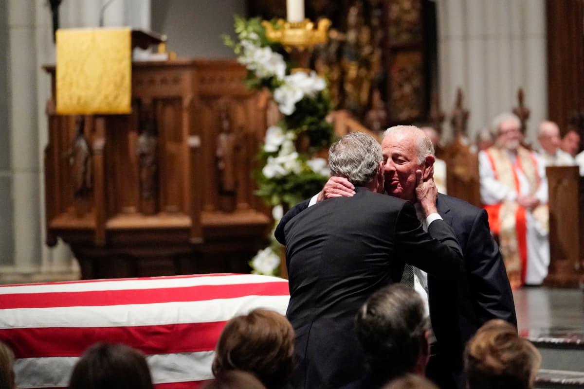 Entinen presidentti George W. Bush syleilee Yhdysvaltain entistä ulkoministeriä James Bakeria tämän pitämän muistopuheen jälkeen.