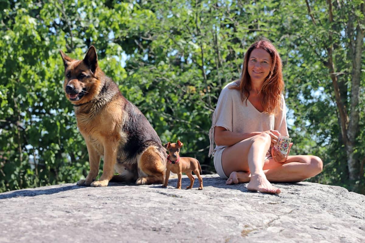 melina Holmberg istuu kalliolla koiriensa kanssa.