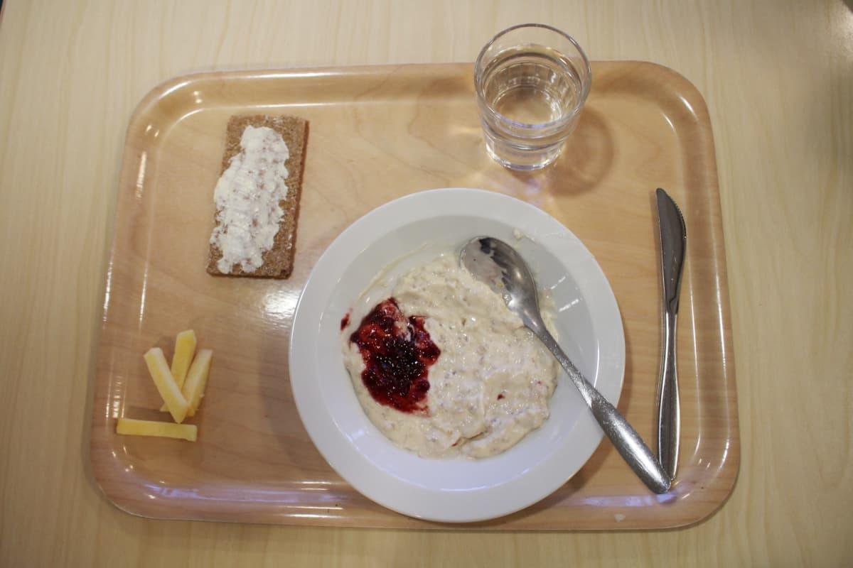 Tarjottimella kouluruokaa: ohrapuuroa, näkkäri ja lasi vettä.