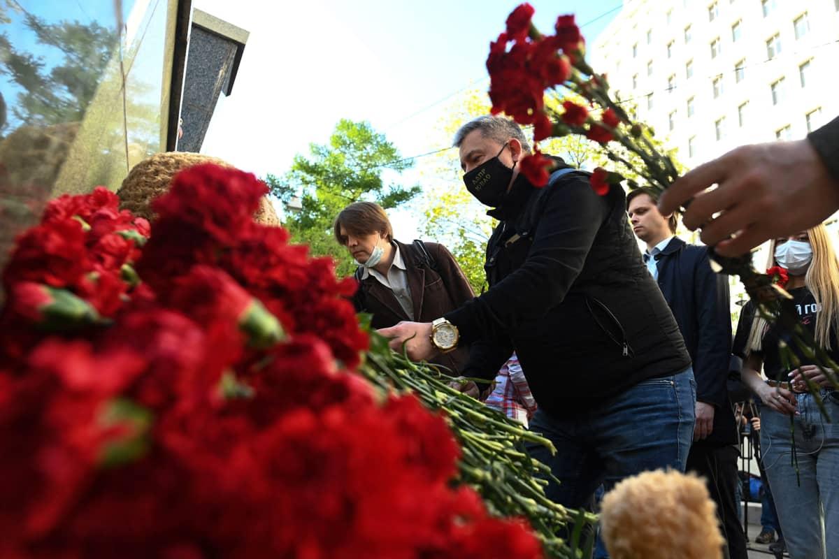Ihmiset jättävät kukkia kouluammuskelupaikalle.