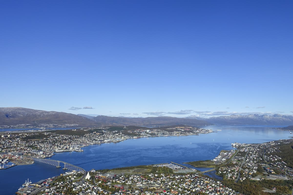 Näkymä Tromssaan. Kuvassa rakennuksia, silta, vettä ja vuoria.