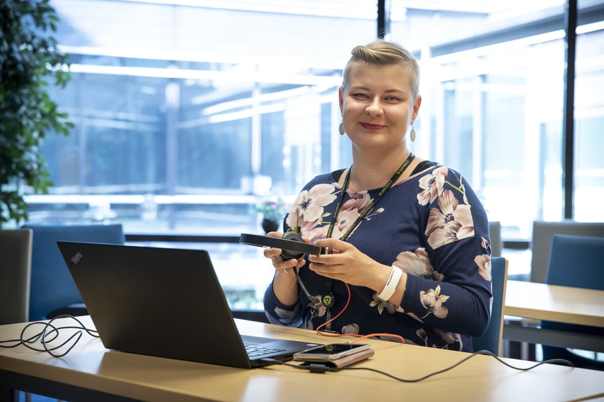 Mari Kivijärvi istuu kuulokkeet kädessään.