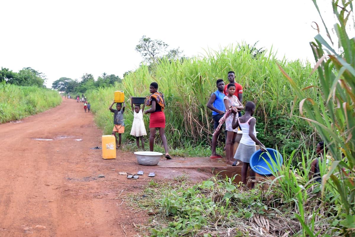 Afrikkalaisia naisia ja lapsia hakemassa vettä joesta