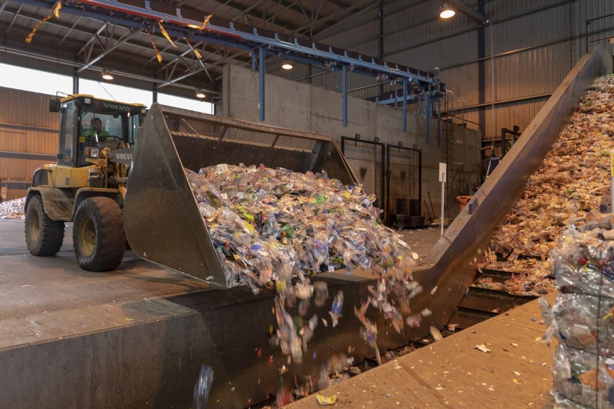Kauhakuormaaja työntää muovipulloja paalauskoneeseen
