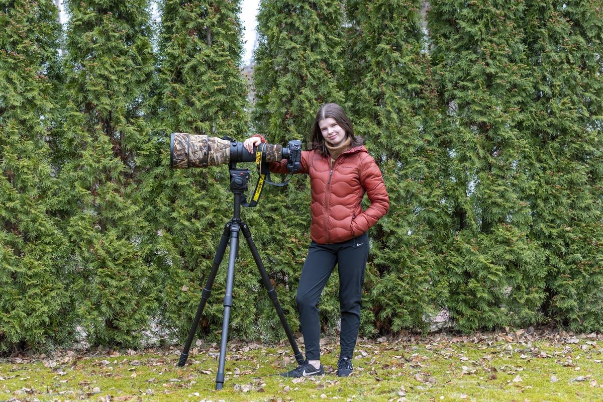 Nuori nainen ison kameran kanssa luonnossa.