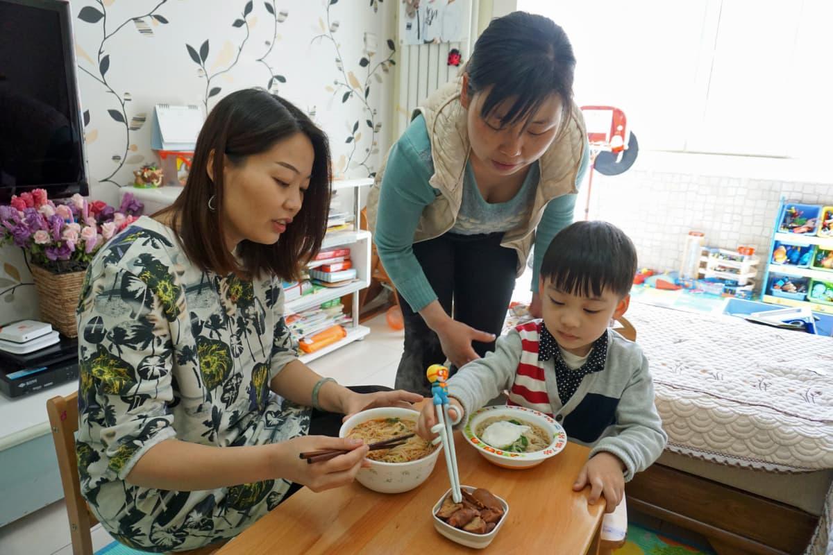 Äiti, poika ja lapsenhoitaja syövät lounasta. Keskiluokkaisen perheen arkea helpottaa niin sanottu ayi eli kotiapulainen (keskellä), joka hoitaa lasta ja tekee kotitöitä.