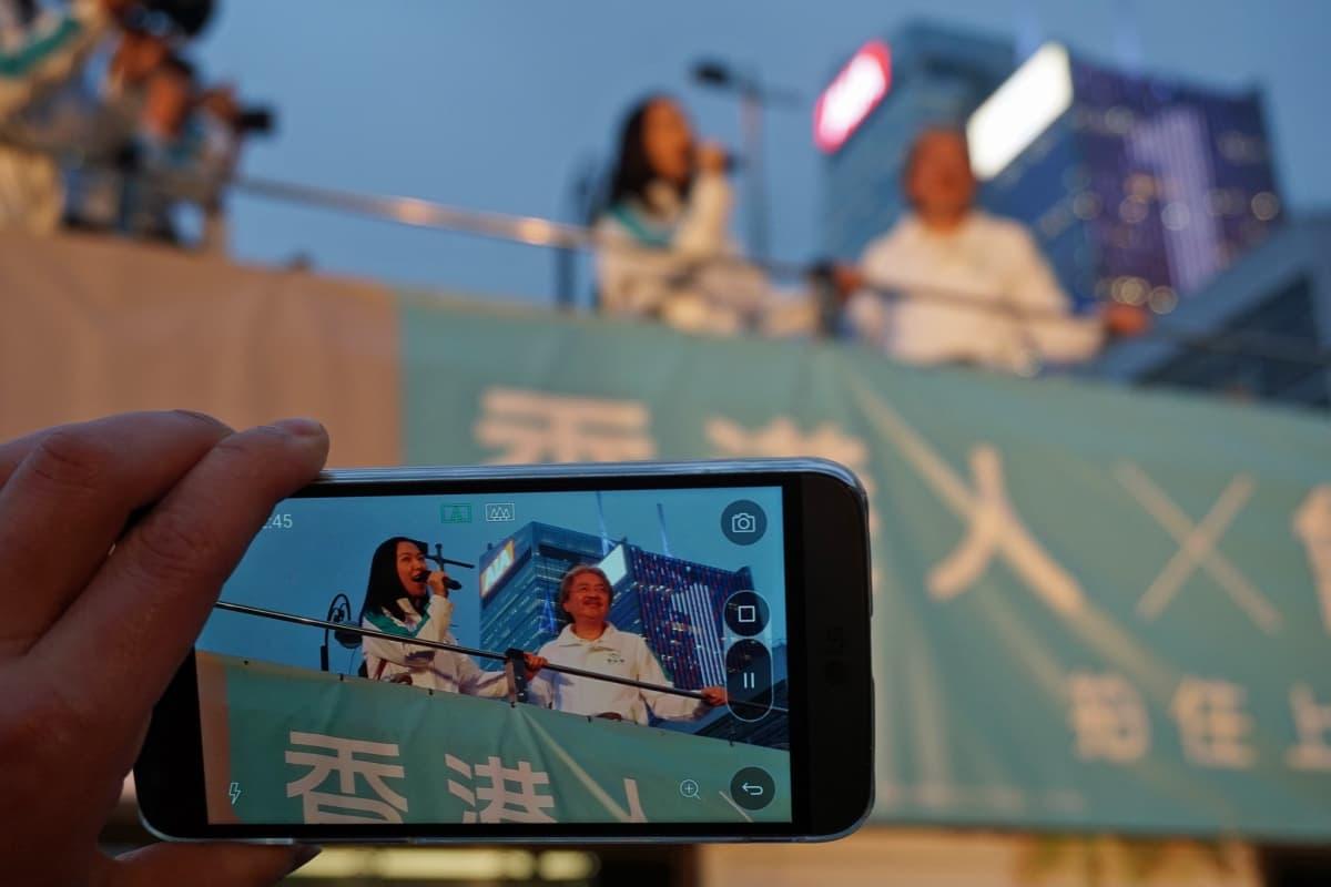 Kännykästä näkyy puhuva John Tsang.