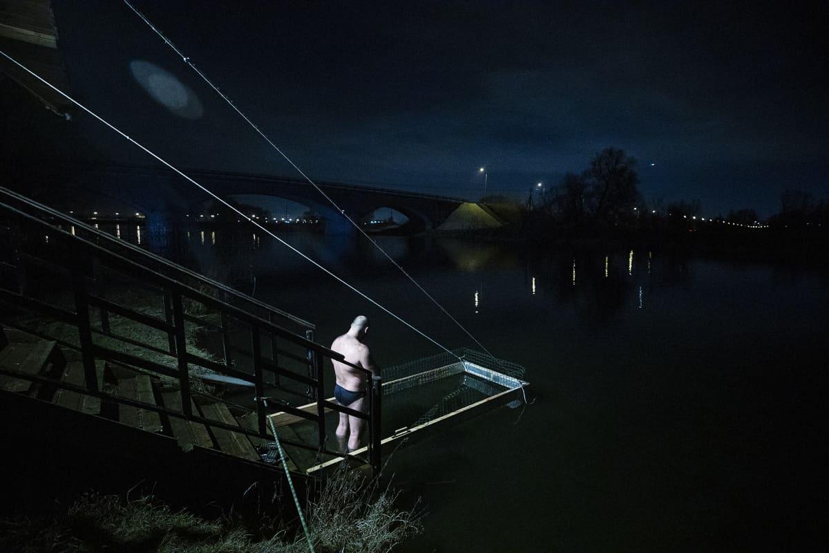 Mies seisoo yöllää veden äärellä ja rukoilee.