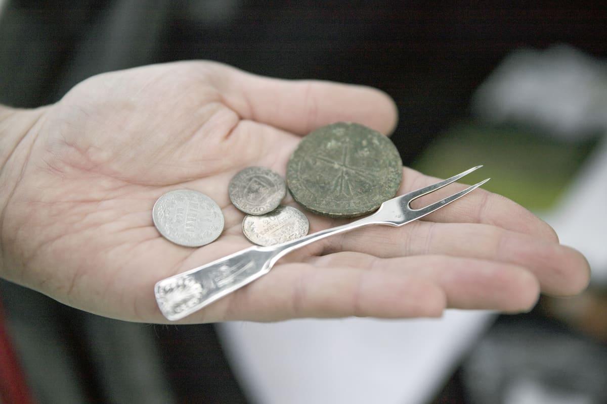 Metallinetsinharrastajan löytöjä. Kolikoita sekä pieni, hopeinen haarukka.