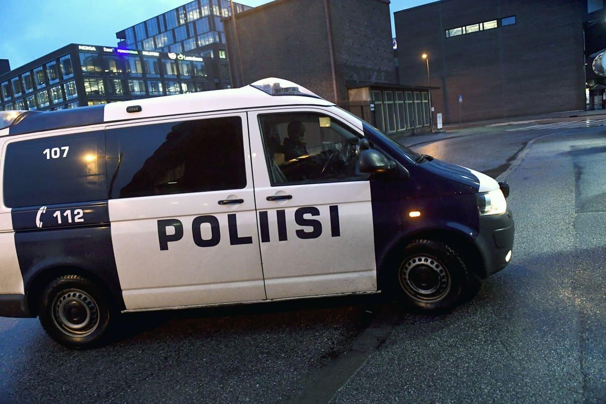 Poliisiauto ajaa oikeustalon portille Helsingissä.