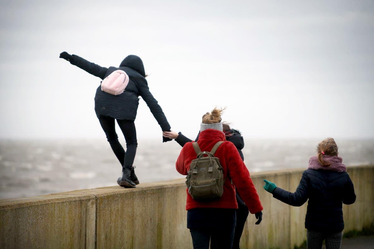 Rantamuurilla kovassa tuulessa tasapainotteleva ihminen, jota pidetään kädestä kiinni.